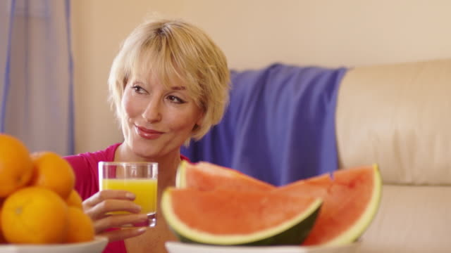 dolly shot of woman with fruit in foreground holding glass of orange juice. - fruit juice stock videos & royalty-free footage