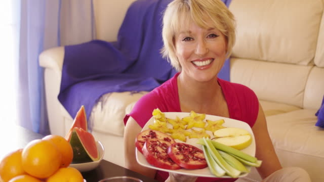 dolly shot of woman with healthy fruit plate. - one mature woman only stock-videos und b-roll-filmmaterial