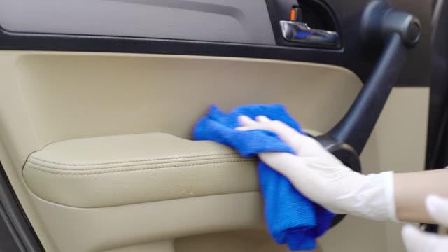 vidéos et rushes de dolly a tiré de la main de la femme dans le gant essuyant les poignées de porte des surfaces du nettoyage intérieur de voiture covit-19 virus. - gant de chirurgie