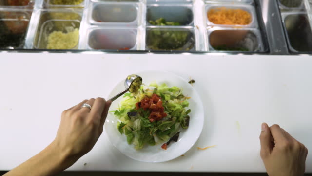 Dolly shot of worker preparing food at kitchen counter in restaurant