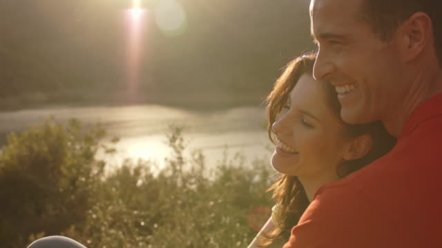 Dolly shot of young couple sitting overlooking lake in sunset.