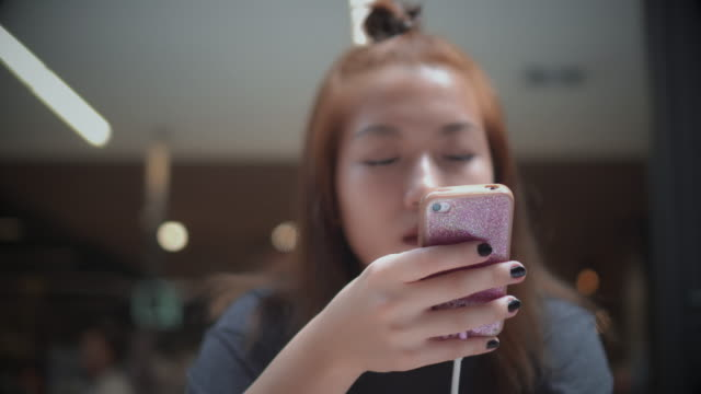 Dolly shot of young woman using smartphone in coffee shop