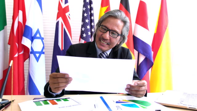dolly shot on front view: dignified and old businessman looking on the results and calling someone on a smartphone on national flag - bandiera dell'argentina video stock e b–roll