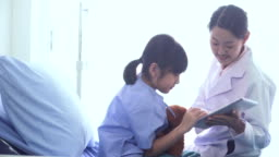 dolly shot on side view: Japanese doctor talking with Thai girl on digital tablet in the hospital ward