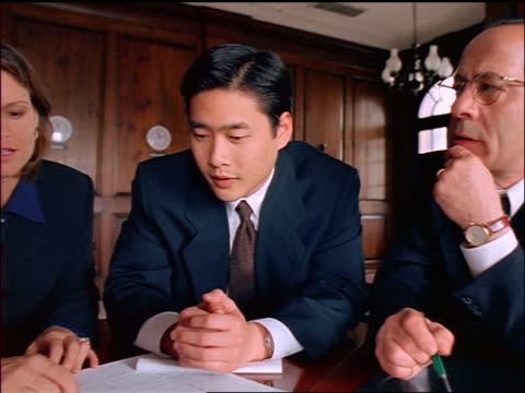 dolly shot out + in businesswoman + two businessmen (one asian) discuss chart/blueprints on table - femmina con gruppo di maschi video stock e b–roll