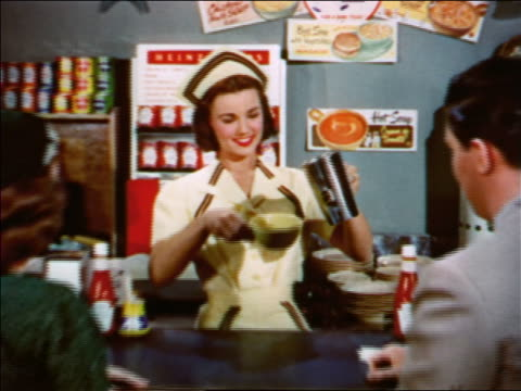 1951 dolly shot out + in of waitress pouring + serving cup of soup to couple at counter in diner - 1950点の映像素材/bロール