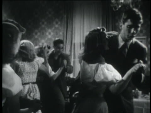b/w 1951 dolly shot out of teenage couples dancing at party / one couple exits room + laughs - 1951 stock videos & royalty-free footage