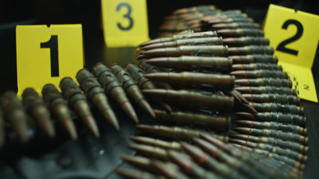 dolly shot over pile of ammunition, assault rifle and evidence tags - extreme close up stock videos & royalty-free footage