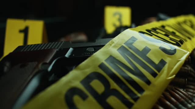 dolly shot over pile of ammunition, firearms, crime scene tape and evidence tags - mord stock-videos und b-roll-filmmaterial