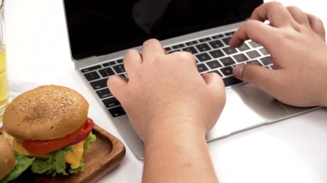 ドリー ショット ハンバーガーやビールなどの不健康な食品のラップトップに入力する太りすぎのタイ実業家の手の肩の上 - unhealthy eating点の映像素材/bロール