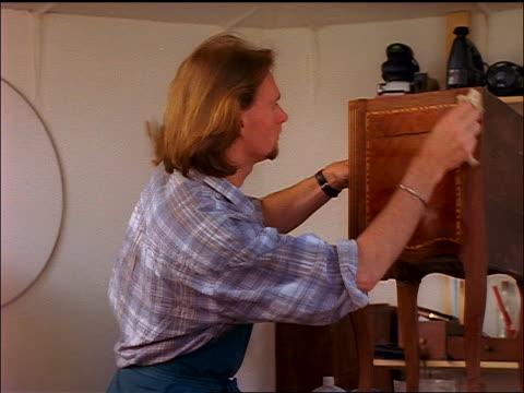 vídeos de stock, filmes e b-roll de dolly shot past blonde carpenter working in shop (refurbishing antiques?) - antiquário loja
