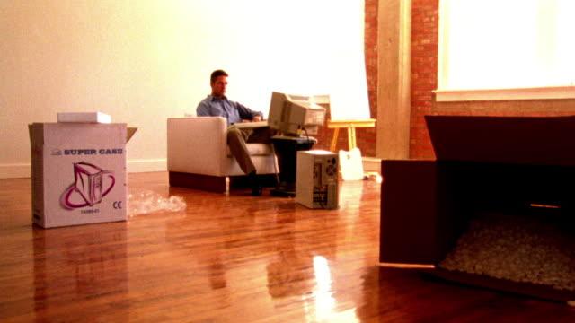 vídeos de stock, filmes e b-roll de high contrast dolly shot past boxes toward man typing on computer in apartment - superexposto