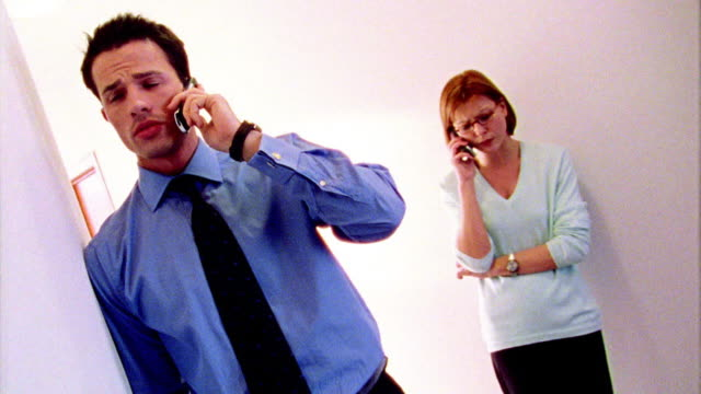OVEREXPOSED CANTED dolly shot past businessman on cell phone toward woman on cell phone behind him