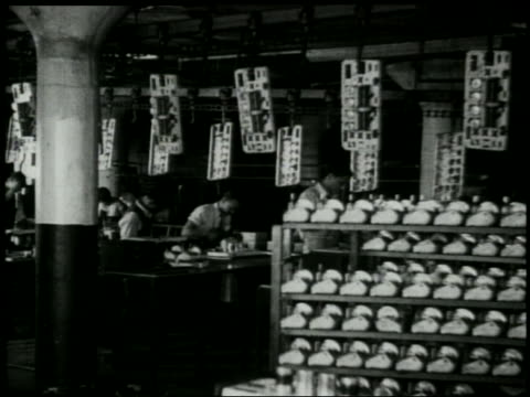 b/w 1929 dolly shot past men assembling radios in factory - 1929 stock videos & royalty-free footage