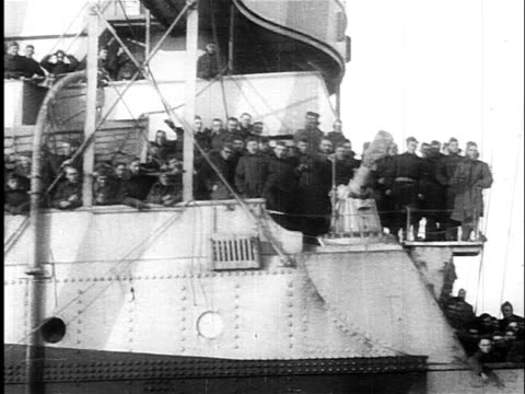 B/W 1918 dolly shot past military ship with waving troops on deck after end of WW I