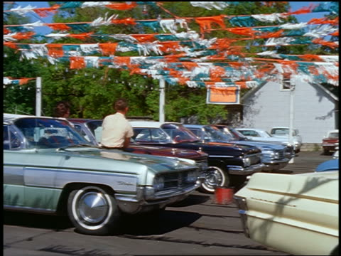 1964 dolly shot past new cars in car lot / couple + salesman - car showroom stock videos & royalty-free footage