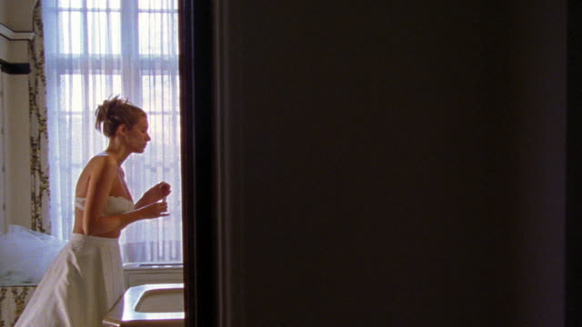 dolly shot past open door of bathroom where woman in long white skirt + bra puts on lipstick in mirror