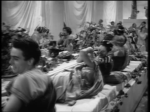 B/W dolly shot past people around table eating + kissing during Roman orgy / Legend of Faust