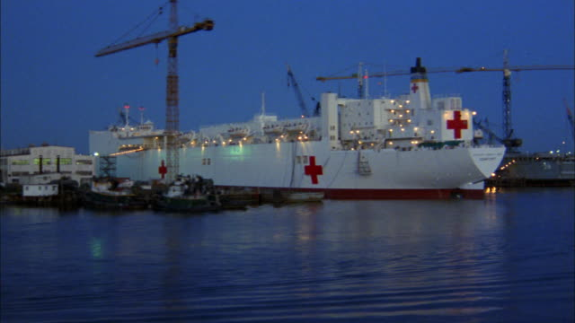 dolly shot past red cross carrier ship and tug boat in harbor - red cross stock videos & royalty-free footage