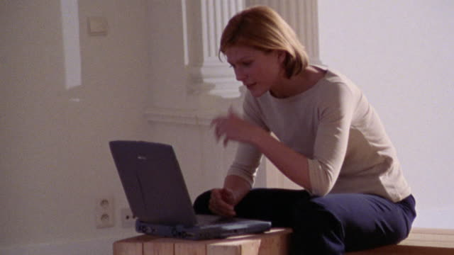 dolly shot past redhead woman typing on laptop on wooden box in empty apartment / pillars in foreground
