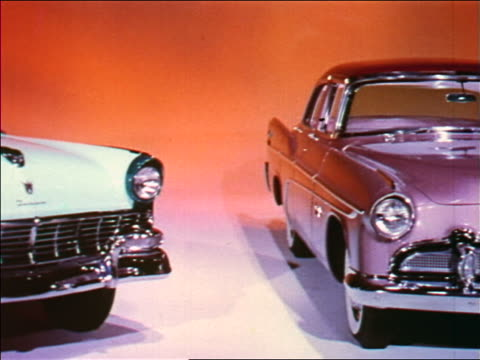 1955 dolly shot past three cars in studio (Ford, DeSoto + Cadillac) / industrial