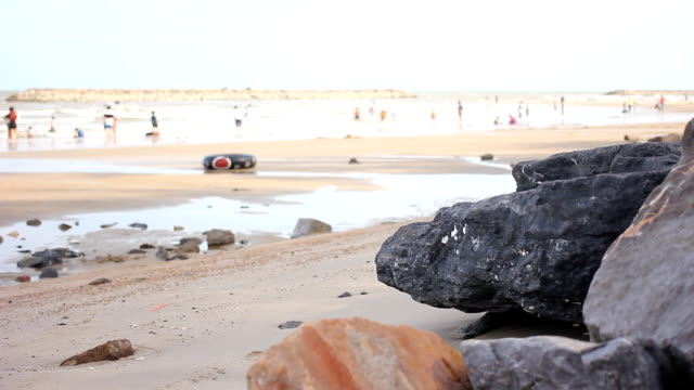 dolly shot: people relaxing on beach. - bugtiger stock videos and b-roll footage