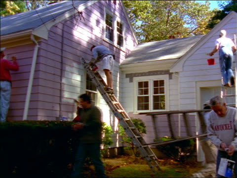 dolly shot person carrying ladder through group of people painting small house exterior lavender - house painter stock videos and b-roll footage