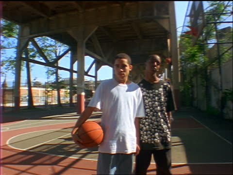 dolly shot portrait 2 black male teens with basketball standing in outdoor court under bridge / brooklyn, ny - basketball stock-videos und b-roll-filmmaterial