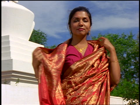 dolly shot PORTRAIT East Indian woman removing sari from head + putting hands in prayer position by stupa