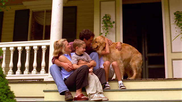 dolly shot PORTRAIT family sitting with golden retriever on porch of house