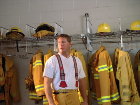 ms dolly shot portrait fireman standing in fire station talking off helmet + looking around room - fire station stock videos & royalty-free footage