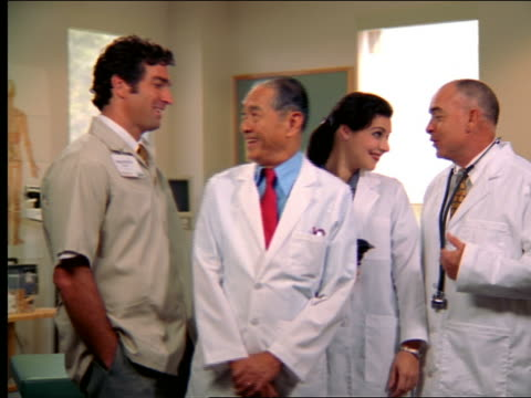dolly shot portrait group of doctors talking + smiling - femmina con gruppo di maschi video stock e b–roll
