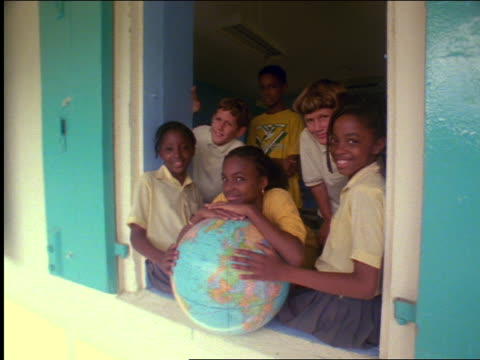 dolly shot portrait group of smiling ethnically diverse children with globe in school window / st. john - global village stock videos & royalty-free footage