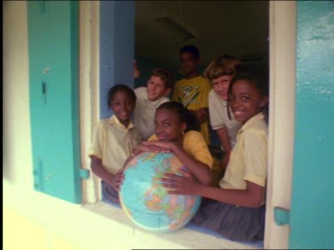 vídeos y material grabado en eventos de stock de dolly shot portrait group of smiling ethnically diverse children with globe in school window / st. john - antillas occidentales