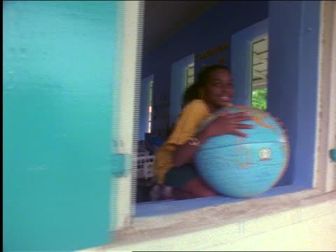 dolly shot portrait laughing black girl leaning on globe in school window / st. john, virgin islands - st. john virgin islands stock videos & royalty-free footage
