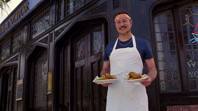 dolly shot portrait man wearing apron + headband holding two dishes of food standing in front of restaurant - sideburn stock videos & royalty-free footage