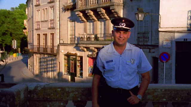 dolly shot portrait of policeman on balcony crossing arms + smiling with street + buildings in background / portugal - portuguese culture stock videos & royalty-free footage