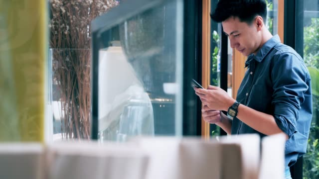 dolly shot :portrait of young asian man buying coffee in a coffee shop. - ordering stock videos & royalty-free footage