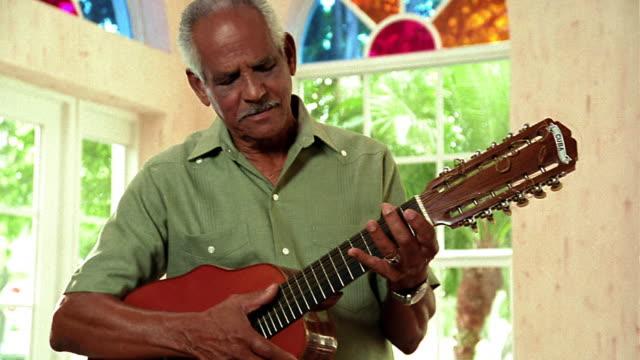 MS dolly shot PORTRAIT senior Hispanic man playing guitar looks up + smiles indoors