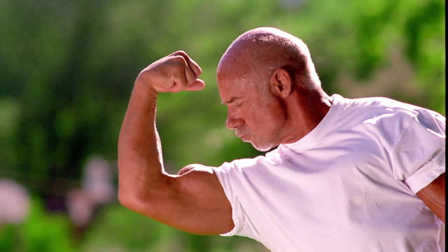 ms dolly shot portrait senior man flexing bicep outdoors - flexing muscles stock videos and b-roll footage