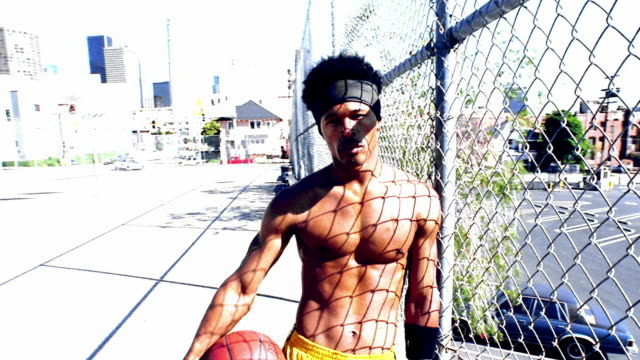 overexposed ms dolly shot portrait shirtless black man leaning against chain link fence holding basketball - hair accessory stock videos & royalty-free footage