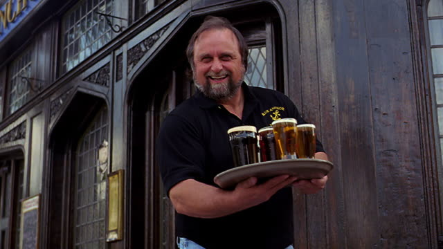 selective focus ms dolly shot portrait smiling man holds serving tray with glasses of beer outside restaurant - tablett oder küchenblech stock-videos und b-roll-filmmaterial