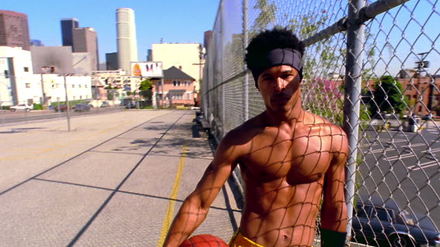 MS dolly shot PORTRAIT toward shirtless Black man leaning against chain link fence holding basketball