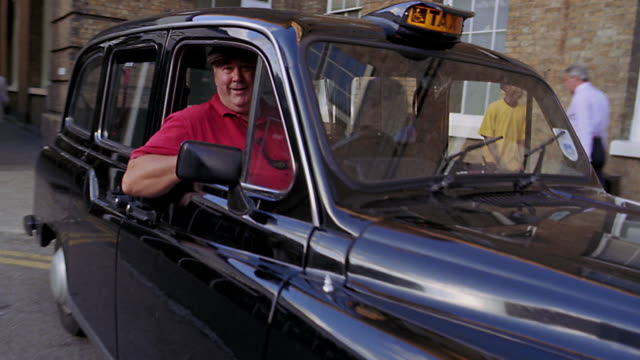 dolly shot portrait toward taxi driver in black taxi tipping hat + smiling / london, england - hackney video stock e b–roll