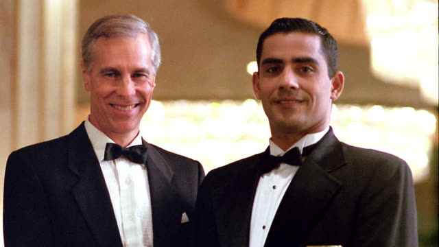MS dolly shot PORTRAIT two men in tuxedos (maitre d' + waiter at restaurant) smiling indoors