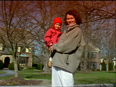 dolly shot PORTRAIT woman holding small child in coat + hat in front of suburban houses with bare trees