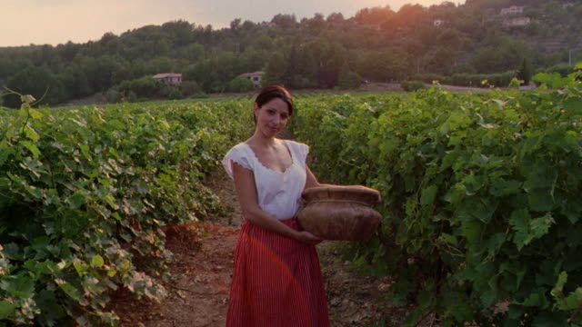 vidéos et rushes de dolly shot portrait woman in traditional clothing standing in vineyard with basket / st. emilion, france - fierté