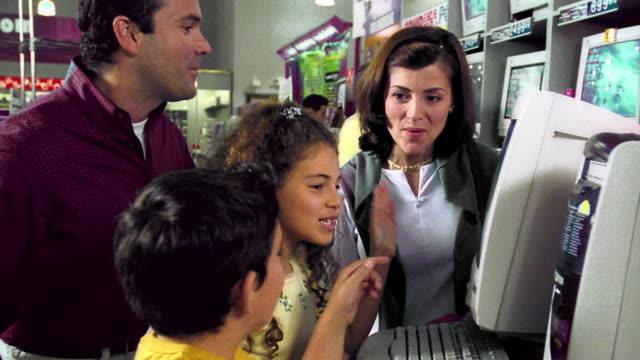 vídeos de stock, filmes e b-roll de ms dolly shot profile hispanic family examining + discussing computer on display in store - loja de produtos eletrônicos