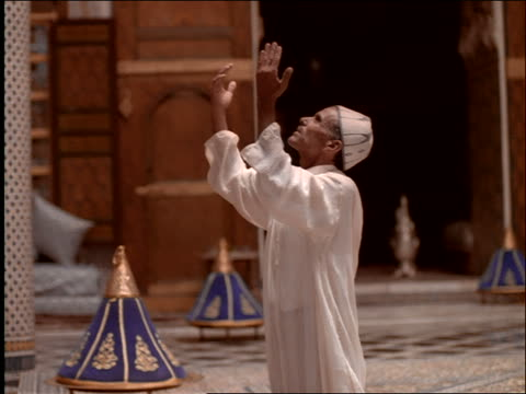 dolly shot profile middle eastern man on knees lifting hands in prayer in mosque / morocco - dish dash stock videos & royalty-free footage