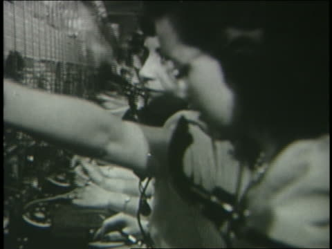 b/w 1946 dolly shot profile row of female telephone operators at switchboard - telephone switchboard stock videos and b-roll footage